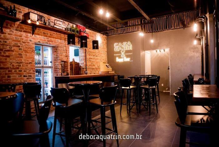 Banquetas, mesas e balcão no bar Casa Gabbi