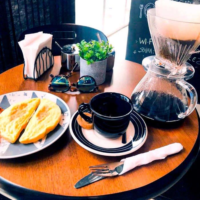 Mesa com café, lanche e talheres