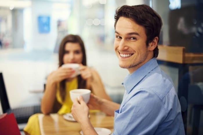 Homem sorrindo tomando café com uma mulher
