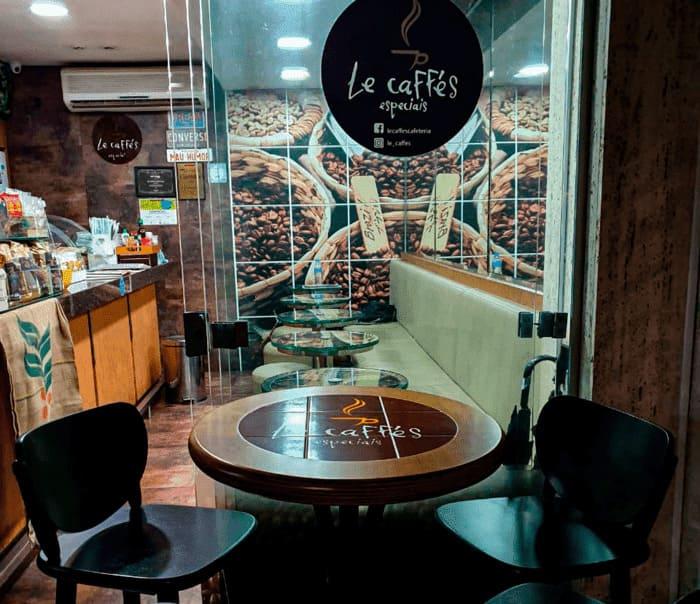 Mesa e banquetas na cafeteria Le Caffés