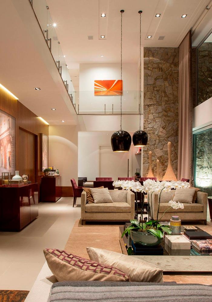 Sala de jantar integrada com sala de estar. Pé direito alto, com spots e dois pendentes pretos