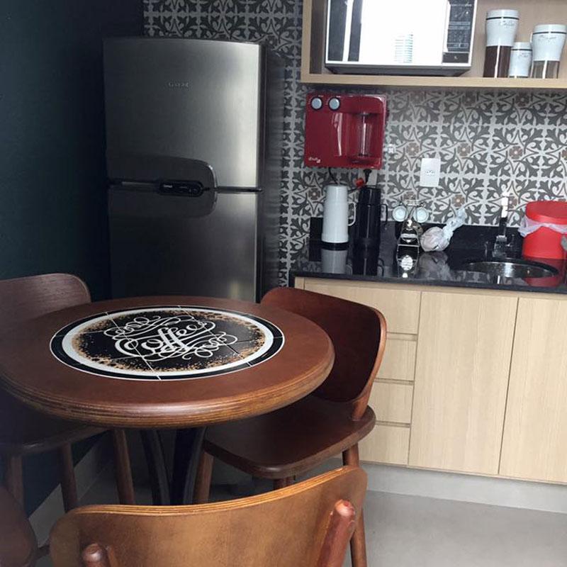 ambiente interno com mesa de madeira e geladeira de inox