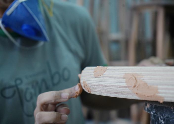 dedo de mulher passando uma espécie de massa sob a madeira