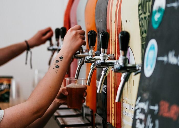 Mãos de clientes se servindo nas torneiras de cerveja disponíveis