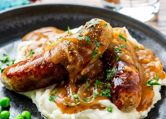 um prato com linguiças e uma quantidade de purê de batata