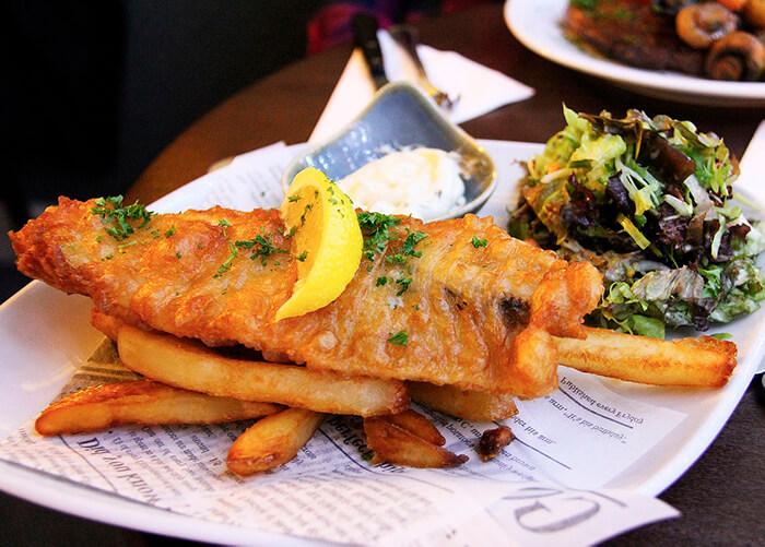 Foto de batata frita e peixe frito acompanhado de um potinho com molho em cima de uma folha de jornal.