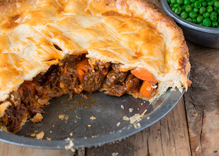 Prato de comida com carne e cenoura em pedaços coberto por uma massa folhada por cima. Pote com ervilhas no canto direito superior.