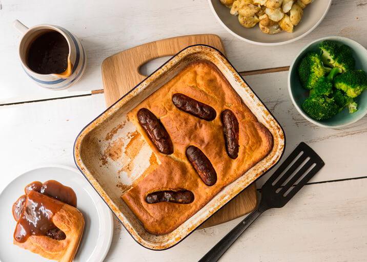 Foto vista de cima de uma mesa com comidas, uma forma de bolo salgado com salsicha, brócolis e molho