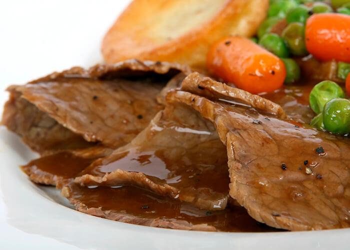 Prato branco de comida com carne, batatas e legumes.