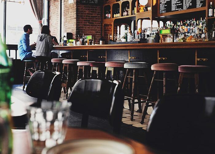 Foto interna de pub aparecendo várias banquetas altas redondas. Ao fundo um homem e uma mulher conversando com o garçom