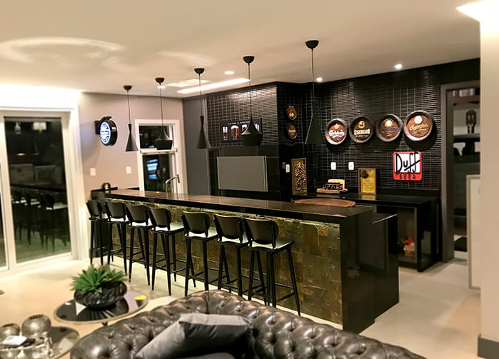 Home Bar com balcão escuro, banquetas altas pretas, quadros com rótulos de cerveja e luminárias pendentes.