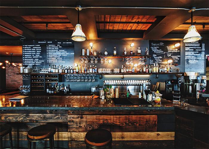 Balcão de Pub em madeira rústica com bebidas e luminárias