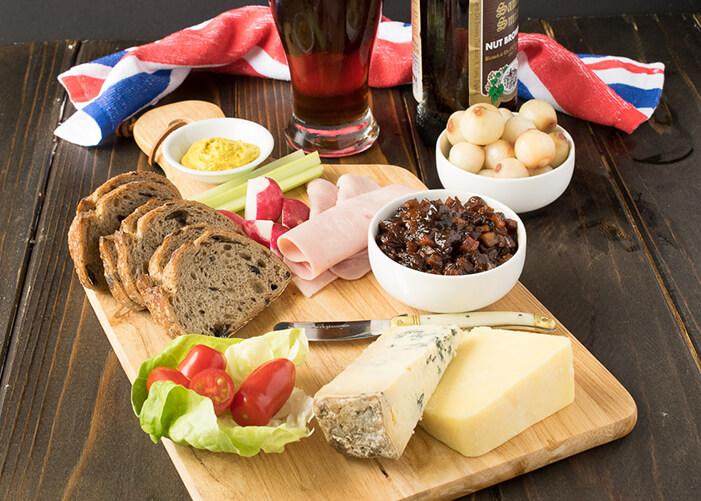 Tábua de cortar carne com salada, queijo, presunto, maçã pão. Cebola em um pote e um copo de cerveja