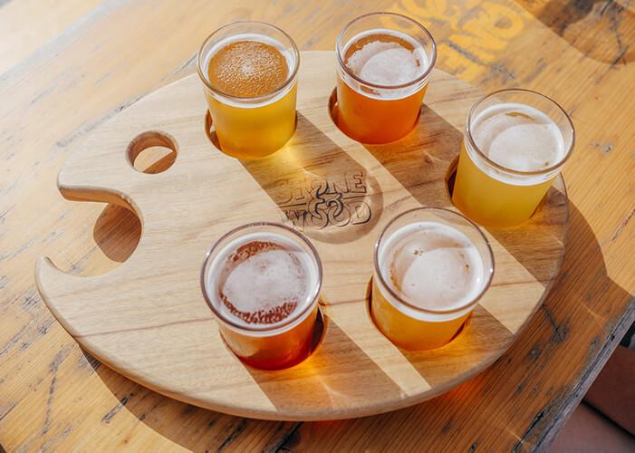 Tábua de madeira com vários copos de cervejas diferentes para degustação.