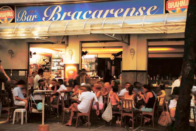 Lado de fora do Bar Bracarense com clientes sentados nas mesas na calçada.