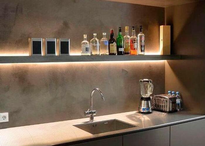 Cozinha cinza com prateleira acima da torneira iluminada com fita de LED