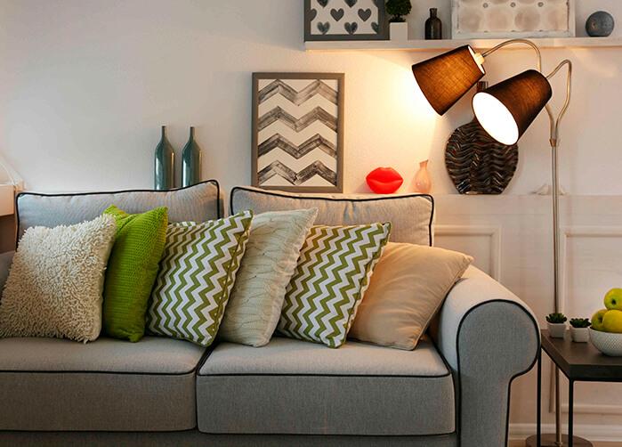 Sala de estar clara, com sofá cinza e almofadas no tom verde