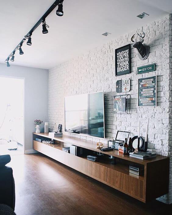 Sala de estar com parede de tijolinho, decoração moderna e trilho de spots no teto