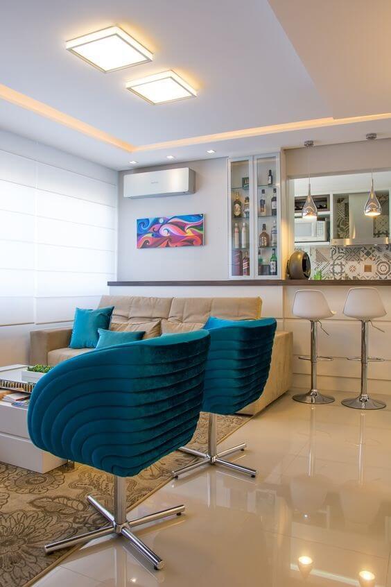 Sala de estar integrada com poltronas azuis em destaque