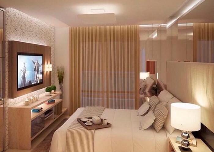 Quarto de casal com decoração nude. Abajur na cabeceira da cama e rack com TV na frente da cama