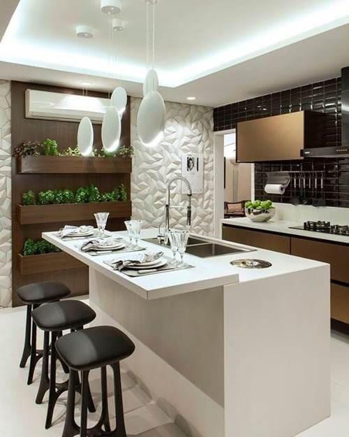 Cozinha com ilha acoplada com bancada branca, banquetas pretas e armários em tom marrom