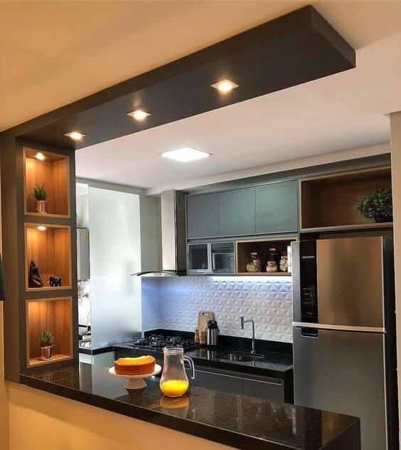 Cozinha pequena integrada com lavanderia. Bancada com mármore escuro.