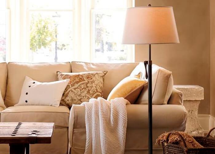 Sala de estar com sofá branco e abajur e cesto de vime para ornamentar