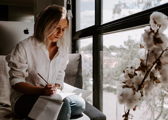 Mulher escrevendo sentada ao lado da janela