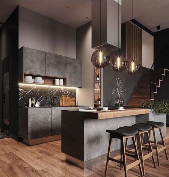 Cozinha escura em tons de madeira e cimento queimado. Lustres na bancada e fita LED na pia