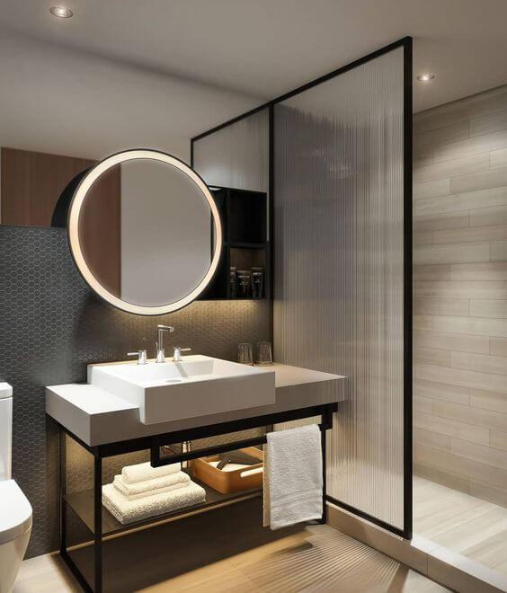 Banheiro moderno em tons de cinza e preto. cuba da pia branca e espelho redondo com luz embutida.