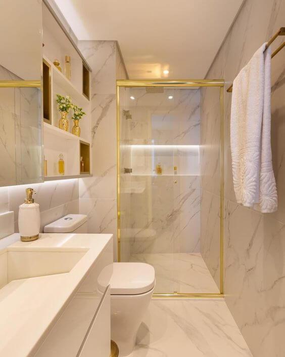 Banheiro com parede e chão com textura de mármore. Box de vidro com estrutura dourada