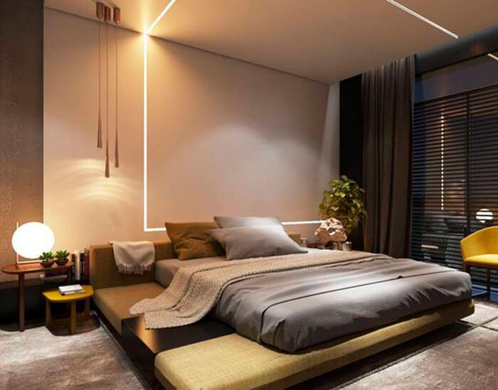 Quarto com rasgo de luz na parede, cama de casal e planta de decoração ao lado