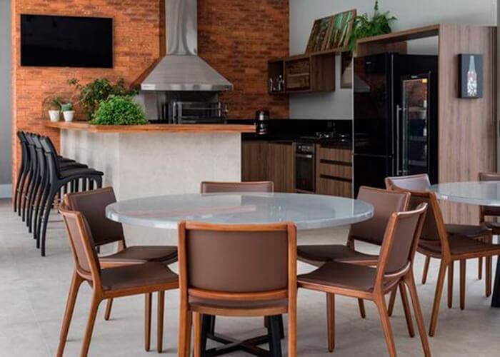 Espaço gourmet em casa com 2 mesas redondas, cadeiras de madeiras estofadas, ao fundo pia em madeira, balcão com baquetas e eletrodoméstico preto