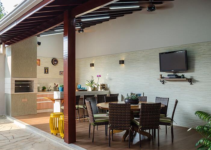 espaço gourmet externo com mesa redonda e cadeiras, bancada com banquetas altas, churrasqueira e balcão de pia. Cores neutras com marrom