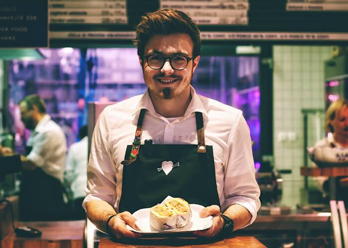 Garçom jovem sorridente, usando óculos, segurando um prato com hotdog.