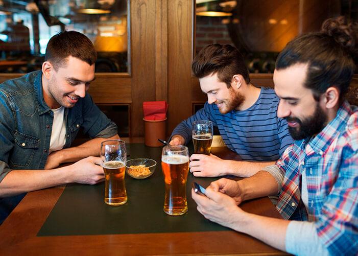 Amigos sentados na mesa do bar, cada um mexendo no seu celular