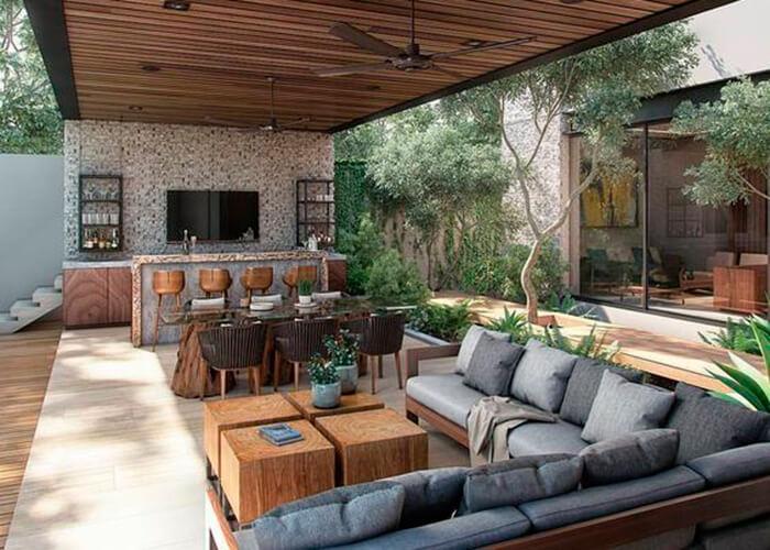 Espaço Gourmet externo com sofá em formato de L nos tons cinzas