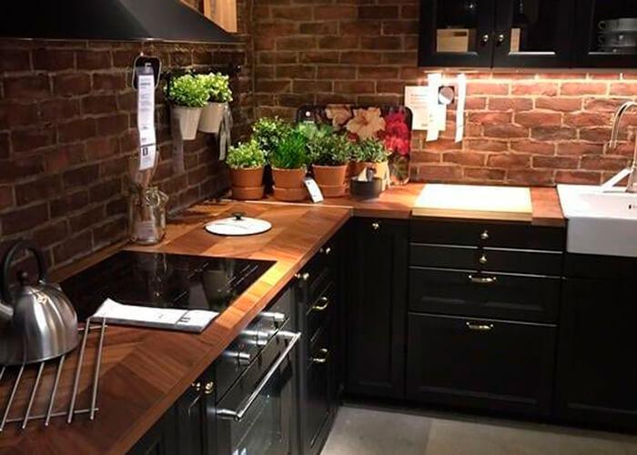 Cozinha preta com madeira, parede de tijolinho, e mini horta em vasinhos de flor