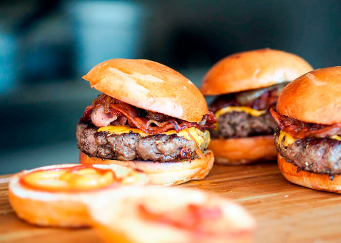 3 hambúrguer de carne prontos para serem servidos e duas fatias de pão aberto com uma fatia de tomate