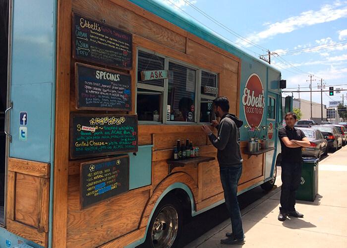 Caminhão Food Truck azul fraco, estacionado na rua. Decorado com quadros negros e madeira. Uma pessoa sendo atendida e uma esperando