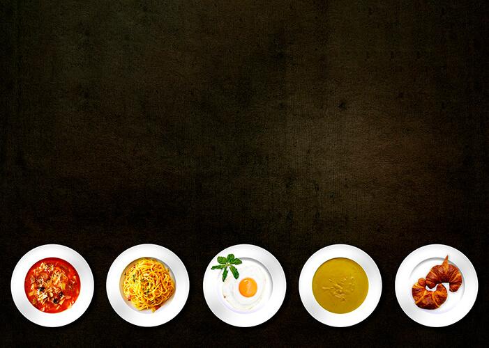 Cinco pratos brancos com comidas diferentes alinhados em fila na parte inferior da foto com fundo marrom dourado