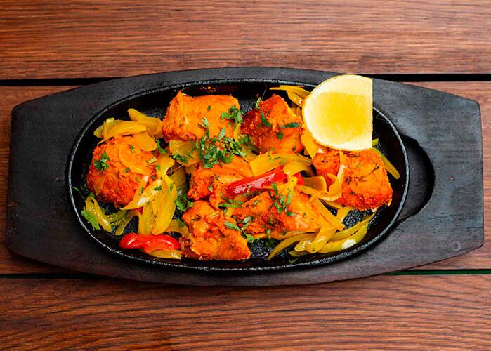 Comida feita com frango em uma bandeja de madeira preta sob uma mesa de madeira marrom. Foto vista de cima