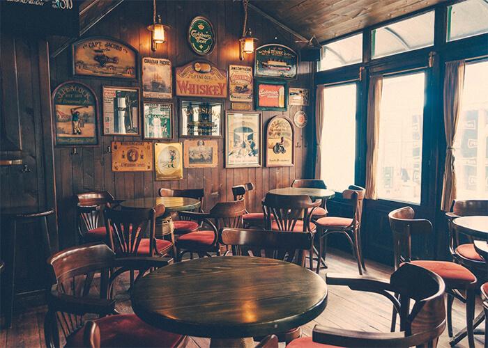 Foto interna de restaurante com mesas redondas, janelas grandes e parede com quadros no estilo texas
