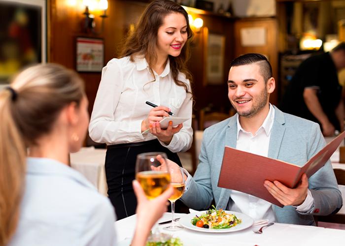 Garçonete sorrindo e atendendo casal na mesa