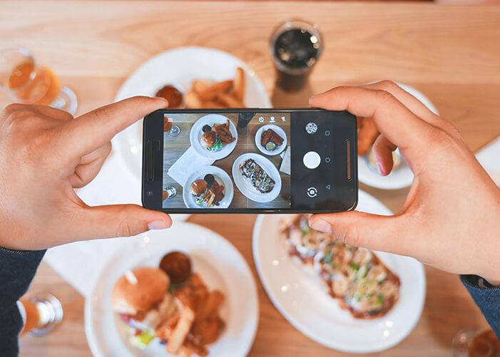 Mãos segurando celular, fotografando 4 pratos com comidas diferentes