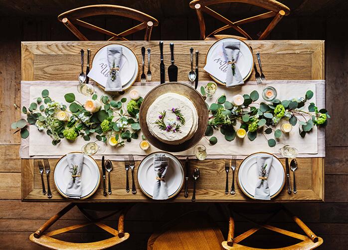 Mesa rústica vista de cima com ornamentos centrais e um bolo. Cinco pratos brancos com guardanapos
