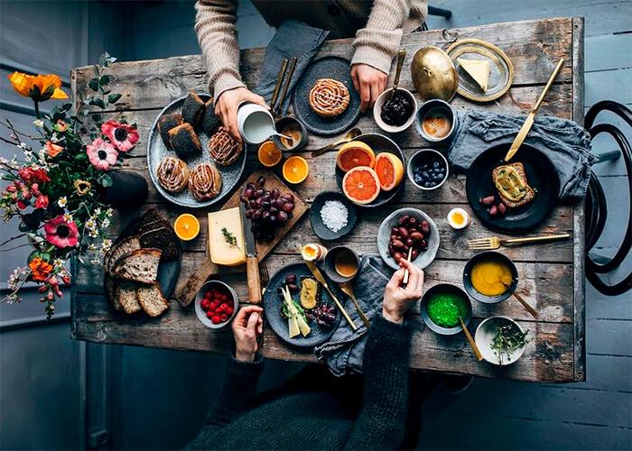 Mesa vista de cima com pratos com comida, talheres, pessoas se servindo