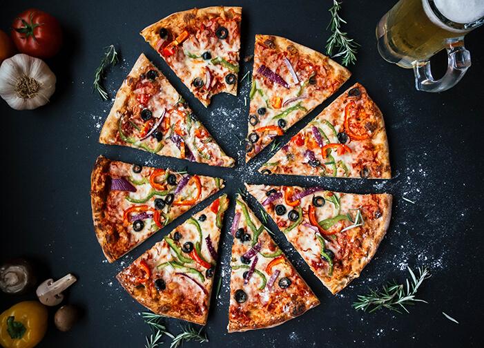 Pizza de queijo, tomate, pimentão verde, azeitona roxa fatiada em um fundo preto ao redor decorando: alho, pimentão, alecrim e um copo com chopp