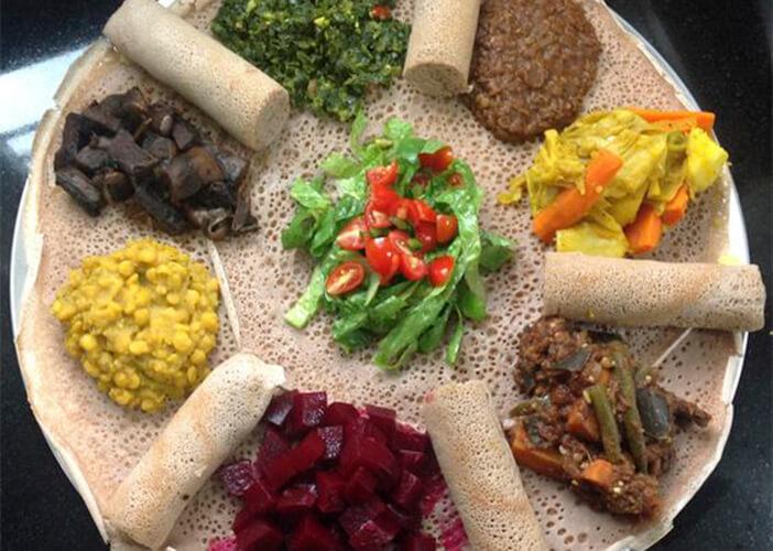 Prato típico da Etiópia com uma massa fininha e recheio em cima de vários molhos e legumes