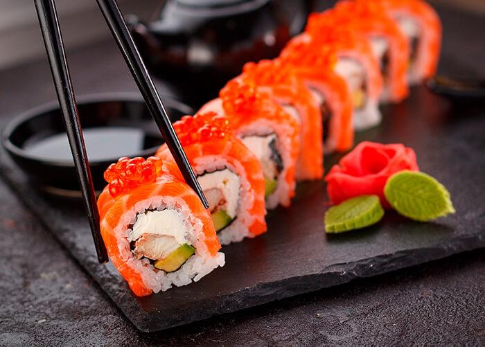 Sushi sendo pegado por um hashi preto ao fundo potinho preto com molho